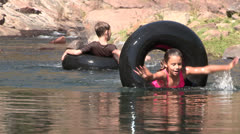 A zoom out shot of two children playing in the river Stock Footage