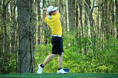 Young golfer tees off Stock Photos