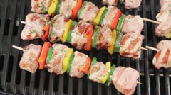 Meat and vegetable kebabs on a grill being brushed with oil marinade Stock Footage