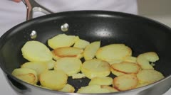 Potato slices being fried in a pan Stock Footage