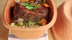 Roast beef with vegetables in a terracotta baking dish Stock Footage