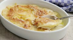 Potato gratin in a baking dish with a spoon Stock Footage