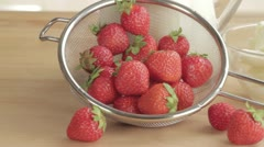 Fresh strawberries in a sieve and a bowl of vanilla ice cream Stock Footage