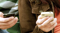 Young boy and girl texting message with mobile phone closeup - stock footage