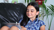 Stock Video Footage of Smiling girl listening to music on tablet pc