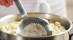Removing spatzle from water with a slotted spoon Stock Footage