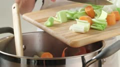 Placing finely chopped soup vegetables into a pan - stock footage