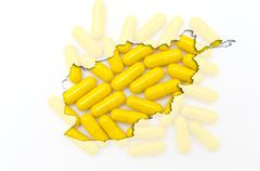 outline map of afghanistan with pills in the background for health and cure - stock photo