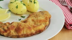 Wiener Schnitzel (breaded veal escalope) with parsley potatoes - stock footage