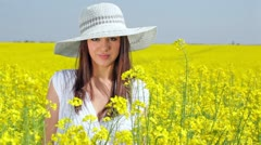 Beautiful girl posing in a field of rapeseed - stock footage