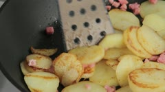 Saute potatoes with lardons in a frying pan Stock Footage