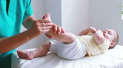 Physiotherapist massaging little baby boy foot - stock footage