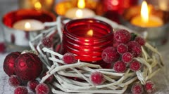 A tealight in a red glass holder and Christmas decorations - stock footage