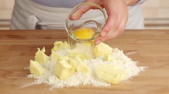 An egg being added to a pile of flour and butter - stock footage