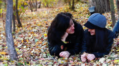 Young woman and teenager laying on leaves Stock Footage