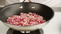 Diced bacon being fried in a pan Stock Footage