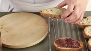 Stock Video Footage of Toasted bread being spread with olive paste