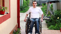 Young man on wheelchair in the yard - stock footage