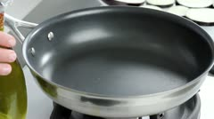 Olive oil being heated in a pan Stock Footage