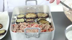 Moussaka being made: aubergine slices and minced meat being layered in a baking - stock footage