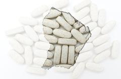 outline map of french guiana with pills in the background for health and cure - stock photo
