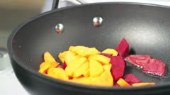 Beetroot and carrots being fried in a pan Stock Footage