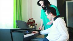 Therapy for young man in wheelchair using piano Stock Footage