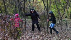 Grandmother playing with granddaughters in the forest Stock Footage