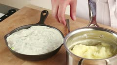 Mashed potatoes being placed on fish pie ingredients Stock Footage