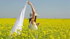 Pretty girl having fun in rapeseed field - stock footage