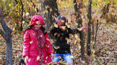 Girls playing in autumn park with leaves Stock Footage