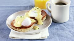 Eggs Benedict (an English muffin with ham, poached egg and Hollandaise sauce, - stock footage