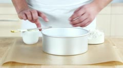 Stock Video Footage of A baking tin being spread with butter and dusted with flour