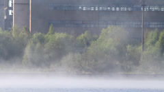 strong fog on the river, factory on the river bank - stock footage