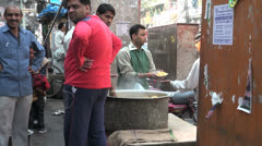 India man dishing out food from a pot Stock Footage