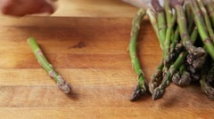 The woody end being broken off green asparagus Stock Footage
