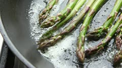 Green asparagus being fried in a pan of butter Stock Footage