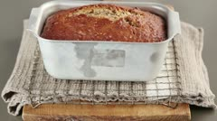 Freshly baked banana bread in a loaf tin - stock footage
