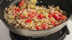 Rice being fried with diced aubergine and tomatoes - stock footage