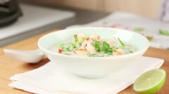 Coconut milk soup being garnished with herbs and chilli rings - stock footage