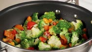 Stock Video Footage of Vegetables in a pan being quenched with vegetable stock (close-up)
