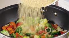 Couscous being added to vegetables (close-up) - stock footage