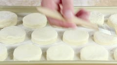 Buttermilk biscuits being brushed with egg yolk Stock Footage