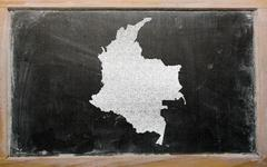 outline map of colombia on blackboard - stock illustration