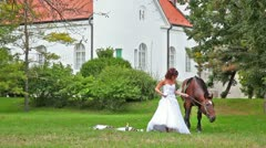 Bride try to walk with a horse, but it is more important to eat Stock Footage