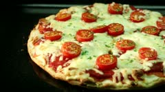 A pizza topped with mozzarella and cherry tomatoes baking in the oven Stock Footage