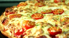 A pizza topped with mozzarella and cherry tomatoes, baking in the oven Stock Footage
