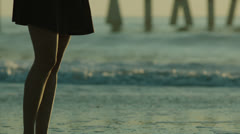 Legs walk past surf break out of focus, slightly handheld, 48fps Stock Footage