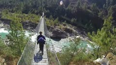 Rear view of male mountaineer at suspension bridge Stock Footage