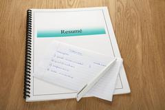resume and interview notes on oak wooden surface - stock photo